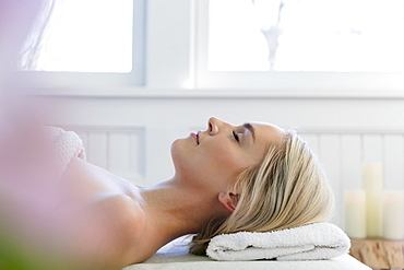 Woman lying on back on massage table with eyes closed