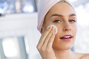 Woman using cleansing pad to wash face