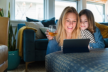 Mother and daughter (6-7) looking at laptop at home