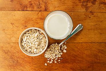 Oats and oat milk against wood