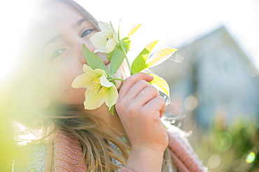 Portrait of girl smelling yellow flowers