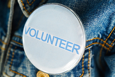 Close up of Volunteer button on denim jacket