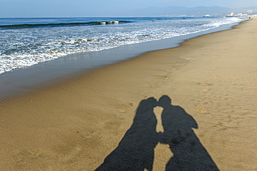 Shadow of couple kissing on Santa Monica Beach