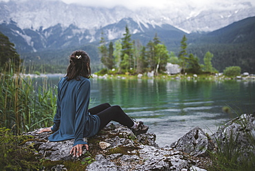 Germany, Bavaria, Eibsee, Young woman sitting on rock at shore of Eibsee lake in Bavarian Alps