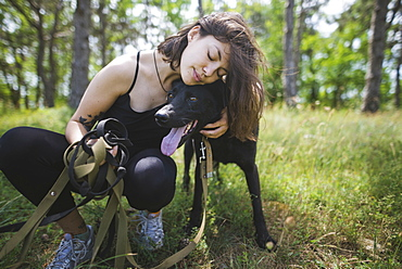 Young woman hugging dog from animal shelter in forest