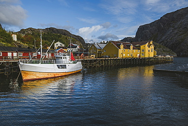 Norway, Lofoten Islands, Nusfjord, Fishing boat in dock in traditional fishing village