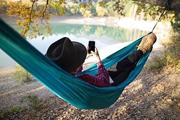 Italy, Man lying in hammock near lake and using smart phone
