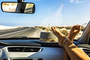 Female feet on dashboard during road trip