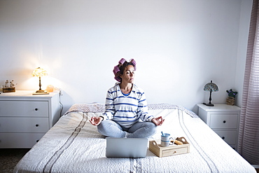 Woman with hair curlers meditating on bed in front of laptop