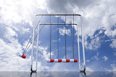 Newtons cradle with capsules