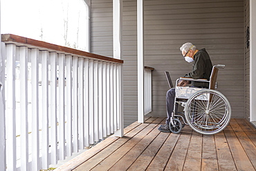 Senior man in wheelchair wearing protective mask to prevent coronavirus transmission using laptop on porch