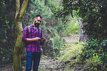 Man using smart phone in forest