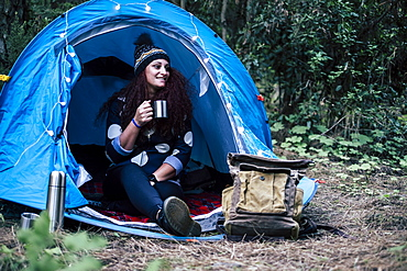 Smiling woman sitting in tent holding cup