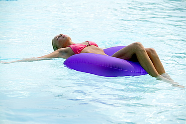 A young woman floating in a pool