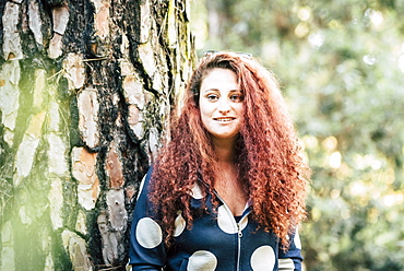 Smiling brown haired woman by tree