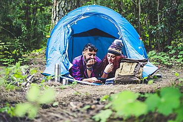 Couple lying in tent using tablet