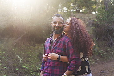 Smiling couple embracing in forest