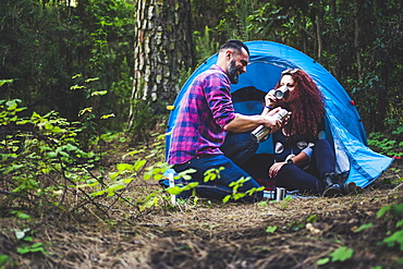 Smiling couple drinking by tent