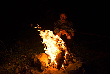 Man sitting by campfire at night