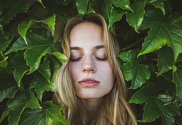 Woman with her eyes closed amongst leaves