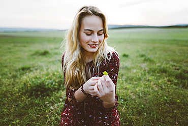 Smiling woman holding flower in field