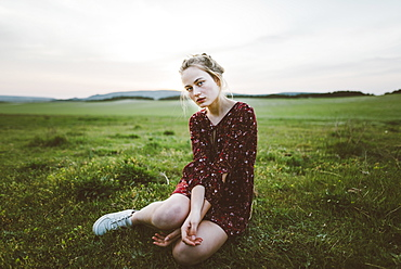 Blonde woman wearing dress sitting in field