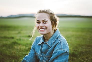 Smiling woman wearing denim jacket in field