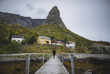 Man walking on bridge by cliff in Lofoten Islands, Norway
