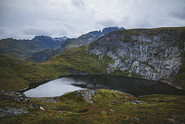 Man standing on rock by lake in Lofoten Islands, Norway