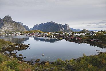 Village by lake and cliffs in Lofoten Islands, Norway