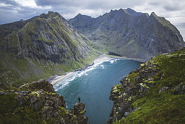 Man standing on cliff at Ryten mountain in Lofoten Islands, Norway