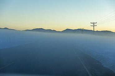 Road in fog at sunrise