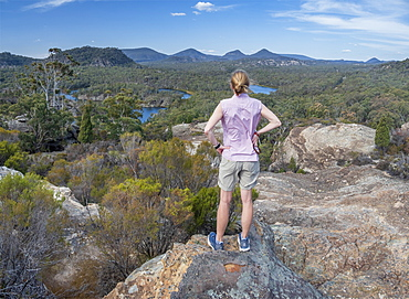 Woman standing on rock by forest