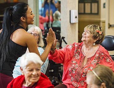 Smiling fitness instructor high-fiving smiling senior woman