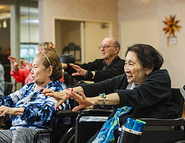 Senior people stretching in wheelchairs