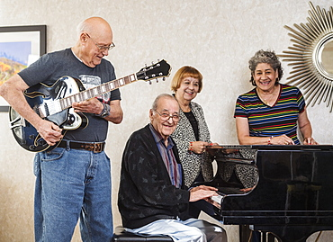 Smiling senior people playing instruments