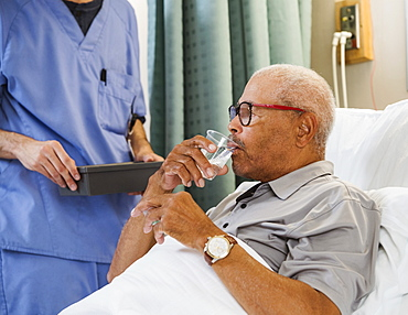 Senior man drinking water in bed