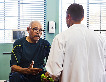 Senior man talking to doctor at rehabilitation center