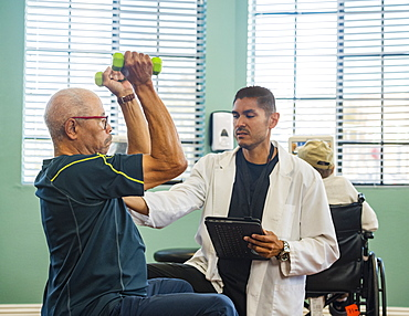 Senior man lifting dumbbells at rehabilitation center