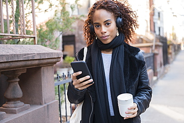 Woman wearing headphones holding smart phone and cup