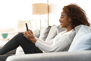 Smiling woman using smart phone on sofa