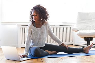 Woman using laptop on yoga mat