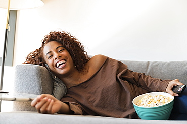 Laughing woman on sofa with TV remote and popcorn