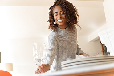 Smiling woman setting dinner table
