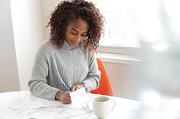 Woman writing in card at table