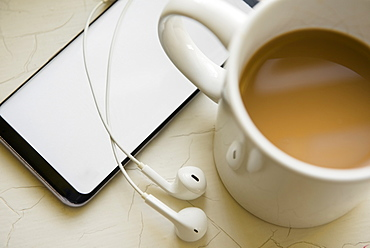 Earphones, smart phone and cup of coffee