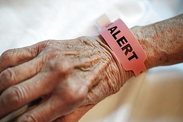 Alert tag around senior person's wrist