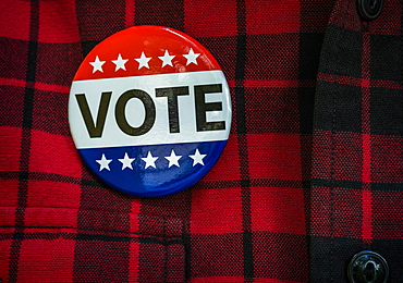 Vote button on red checked shirt