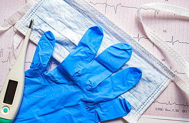Latex glove, hygiene mask and thermometer on electrocardiogram