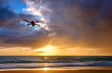 Drone flying over beach at sunset
